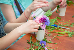Outdoors floristic workshop. Zaporizhia/Ukraine- May 28, 2017: Charity Family festival:  closeup hands of girl, participating at floristic workshop, learning to Royalty Free Stock Photo