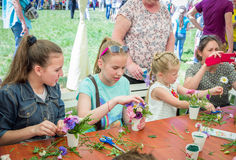 Outdoors floristic workshop. Zaporizhia/Ukraine- May 28, 2017: Charity Family festival:  teen girls participating at floristic workshop, learning to arrange Royalty Free Stock Photography