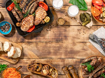 Outdoors Food Concept. Barbecued steak, sausages and grilled veg. Outdoors Food Concept. Appetizing barbecued steak, sausages and grilled vegetables on a wooden Royalty Free Stock Photography