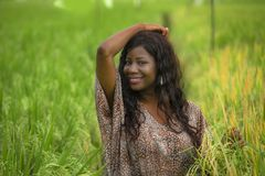 Outdoors fresh portrait of young beautiful and happy black afro American woman in cool dress having fun at tropical rice field. Enjoying exotic holidays trip in stock photo
