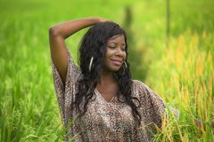 Outdoors fresh portrait of young beautiful and happy black afro American woman in cool dress having fun at tropical rice field. Enjoying exotic holidays trip in royalty free stock photography
