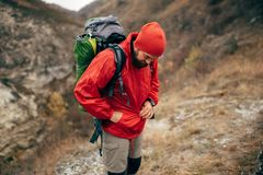 Outdoors image of  extreme hiker man hiking in mountains with travel backpack. stock photos