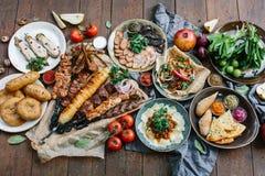 Outdoors karmowy pojęcie Apetyczny barbecued stek, kiełbasy i piec na grillu warzywa na drewnianym pyknicznym stole, obraz royalty free
