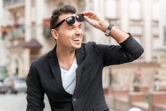 Outdoors leisure. Young man in suit standing on city street taking sunglasses off smiling surprised close-up stock photography