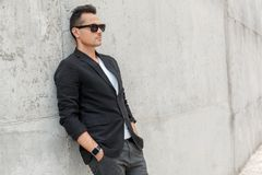 Outdoors leisure. Young man in suit and sunglasses on city street isolated leaning on wall serious stock photography