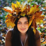 Outdoors lifestyle close up portrait of charming young woman wearing a wreath of autumn leaves. walking on the autumn. Park royalty free stock image
