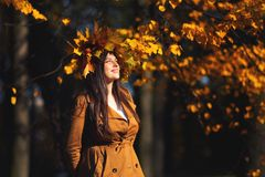 Outdoors lifestyle close up portrait of charming young woman wearing a wreath of autumn leaves. walking on the autumn stock image