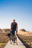 Outdoors lifestyle image of travelling man with cute dog. Tourism concept. Royalty Free Stock Photography