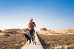 Outdoors lifestyle image of travelling man with cute dog. Tourism concept. Stock Photos