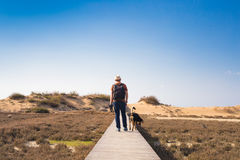 Outdoors lifestyle image of travelling man with cute dog. Tourism concept. Stock Photo