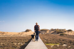 Outdoors lifestyle image of travelling man with cute dog. Tourism concept. Royalty Free Stock Image