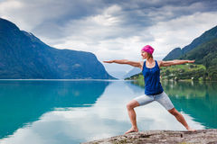 Outdoors meditation. Relaxed young yoga woman in yoga pose near the lake royalty free stock images