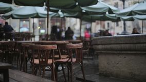 Moody rainy cafe. Outdoors moody cafe with wet tables and chairs, rainy evening stock video