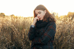 Outdoors noon portrait of thoughtful young beautiful redhead woman in scarf and jacket on faded meadow background Royalty Free Stock Photography