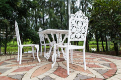 Outdoors patio with furniture. White iron chair in garden with trees Royalty Free Stock Photography