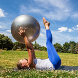 Outdoors pilates exercise for young blond woman Royalty Free Stock Images
