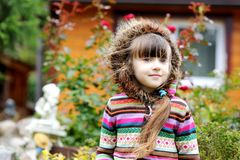 Outdoors portrait of adorable child girl in hood Stock Photos