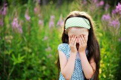Outdoors portrait of adorable confused child girl. Hiding her eyes under palms Royalty Free Stock Image