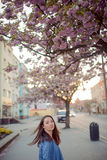 Outdoors portrait of beautiful smiling woman model in pink blossoms on spring day Royalty Free Stock Photo