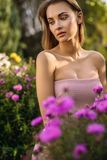 Outdoors portrait of beautiful young woman in casual clothes posing in autumn garden Stock Image