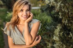 Outdoors portrait of beautiful young woman in casual clothes posing in autumn garden Royalty Free Stock Photo