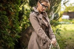 Outdoors portrait of beautiful young woman in glasses in autumn garden. Stock Photos