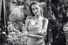 Outdoors portrait of beautiful young woman posing in autumn garden. Black-white photo. Royalty Free Stock Image