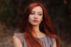 Outdoors portrait of beautiful young woman with red hair Royalty Free Stock Image