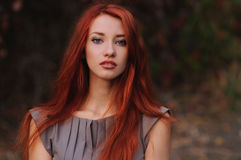 Outdoors portrait of beautiful young woman with red hair. Colorful autumn royalty free stock image