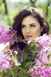 Outdoors portrait of Brunette young woman in lilac flowers, spri Royalty Free Stock Image