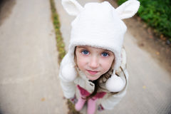 Outdoors portrait of a child girl in warm hat. Full length portrait of amazed child girl wearing warm white hat, focus on face Royalty Free Stock Photo