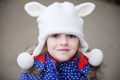 Outdoors portrait of a child girl in warm hat. Outdoors portrait of amazed child girl wearing warm white hat Stock Photos