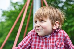 Outdoors portrait of cute preschool boy at the playground on natural green background.  stock photos