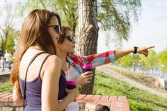 Outdoors portrait of female friends drinking coffee and having fun, women looking into the distance, pointing with fingers. royalty free stock photo