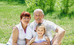 Outdoors portrait of grandparents with granddaughte stock images