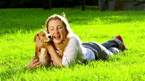 Outdoors portrait happy woman with a dog beagle. Playing on nature. Slow motion stock video