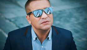Outdoors portrait of a man is wearing sunglasses. Outdoors portrait of a middle aged man is wearing sunglasses and looking at skyscrapers Stock Photo