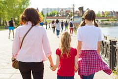 Outdoors portrait of mother and two daughters. Holding hands walking down the street, back view royalty free stock photography