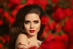 Outdoors portrait of Natural Beauty woman in red roses. Sensual Stock Images