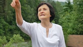 Outdoors portrait of an older woman with short dark hair and wrinkled face pointing at something during her trip to the stock video footage