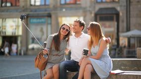 Outdoors Portrait of One Man and Two Women Photographing Themselves Using Smartphone and Selfie Stick. Outdoors Portrait of One Man and Two Women Photographing stock video