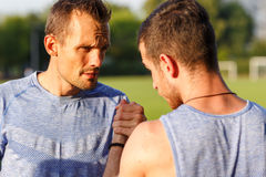 Outdoors portrait of serious strong men shake hands before competition Royalty Free Stock Photo
