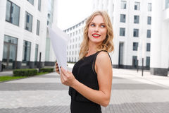 Outdoors portrait of smiling attractive business woman with contract Royalty Free Stock Photography