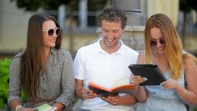 Outdoors Portrait of Three Smiling Students Talking and Studing Together Outdoors Sitting on the Bench. Two Girls and stock video footage