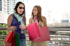 Outdoors portrait of two fashion colorful shoppers having fun together with bags shopping. In the city background stock images
