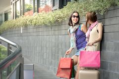 Portrait of two fashion colourful shoppers having fun together with bags shopping. Outdoors portrait of two fashion colourful shoppers having fun together with royalty free stock photography