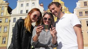 Outdoors Portrait of Two Girls and One Man with Dark Mobile Phone in Brunette s Hand. Three Friends Using Smartphone on. Old Buildings Background During Sunny stock footage
