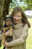 Smiling happy senior woman case of puppy love holding baby dog