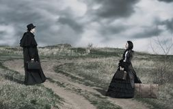 Outdoors portrait of a victorian lady in black and gentleman. stock image