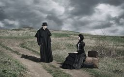 Portrait of a victorian lady in black sitting on the road with her luggage and gentleman standing nearby. stock photography